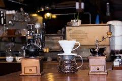 Broyeur de café avec des grains de café en verre sur la table Images libres de droits