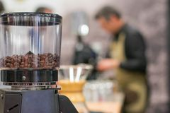 Broyeur de café avec le barman brouillé à l'arrière-plan image libre de droits