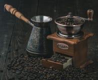 Broyeur de café et jezva avec des grains de café sur le fond foncé images libres de droits