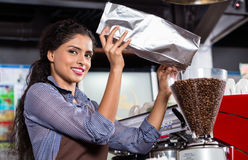 Broyeur de café remplissante de barman indien Photos stock