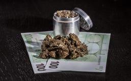 Broyeur en métal avec la marijuana et l'argent Photo libre de droits