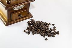 Broyeur et une poignée de grains de café Image stock