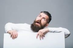 Bärtiger überraschter Mann mit Papier Stockfoto