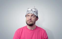 Bärtiger lustiger Mann in einer Kappe der Aluminiumfolie Stockfotos
