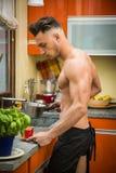 Bärtiger Mann im Schutzblech, das Frühstück zubereitet Lizenzfreie Stockfotos