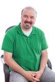 Bärtiger Mittelalter-Mann, der auf seinem Stuhl lächelt Stockbilder