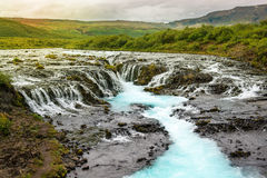 Bruarfoss waterfall with turquoise water cascades at sunset, Ice Stock Photos