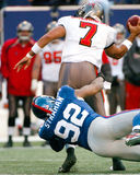 Bruce Gradkowski hit by Michael Strahan. Tampa Bay Buccaneers QB Bruce Gradkowski #7 is hit from behind by New York Giants DE Michael Strahan. (image taken from Royalty Free Stock Images