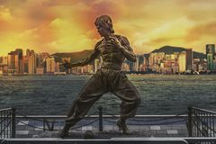 Bruce Lee statue at the Avenue of Stars. Skyline over Victoria Harbour in the background at sunset. royalty free stock images