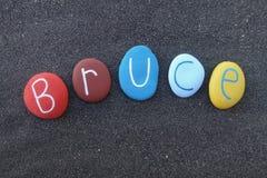 Bruce, nombre dado masculino con las piedras coloreadas sobre la arena volcánica negra Fotografía de archivo