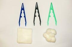 Brucelles, tampons de coton et morceaux médicaux de gaze Photographie stock libre de droits