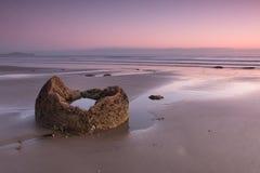 Bruch eines Flusssteins auf dem Ozeanufer bei Sonnenaufgang Lizenzfreies Stockbild