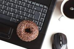 Bruch im Büro. Krapfen auf Laptoptastatur stockfotos