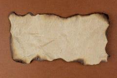 Bruciato di carta su fondo marrone Immagini Stock Libere da Diritti