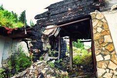 Bruciato fuori alloggi con le capriate carbonizzate del tetto e la mobilia bruciata Fotografia Stock