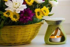 Bruciatore a nafta con i crisantemi dal lato Bruciatore di Aromatherapy Lubrifichi, bruciatore di aromaterapia, fiori e candele p fotografia stock