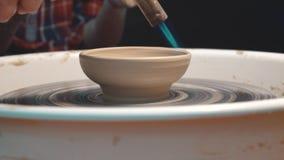 Bruciatura di un piatto dell'argilla su un tornio da vasaio video d archivio