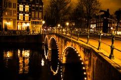 Brud över en kanal i Amsterdam på natten royaltyfri bild