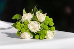 Brud- blommabukett på den vita tabellen på svart bakgrund royaltyfri foto