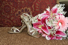 Brud- bröllopskor och bukett Arkivfoton