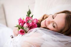 Brud: Bruden dagdrömmer på soffan med buketten Royaltyfria Bilder