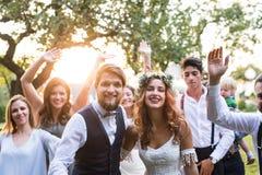 Brud brudgum, gäster som poserar för fotoet på bröllopmottagandet utanför i trädgården arkivbilder