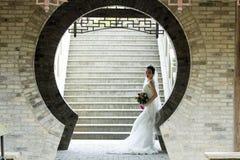 Brud- bukett för brudhåll med den vita bröllopsklänningen nära en tegelstenbåge Royaltyfri Foto