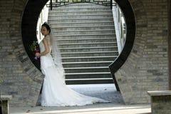 Brud- bukett för brudhåll med den vita bröllopsklänningen nära en tegelstenbåge Arkivbild