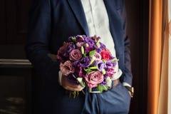 Brud- bukett i händer som gifta sig buketten i händer av brudgummen, Royaltyfria Bilder