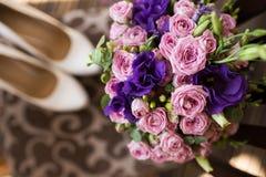 Brud- bukett med rosa färg- och lilablommor Garters och strumpor Brud i den vita klänningen Morgon för brud` s Arkivbild