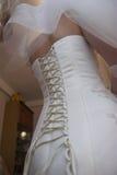 Brud`en s korsetterar i en vit lång bröllopsklänning arkivfoto