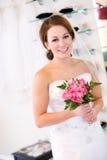 Brud: Hållande bukett för kvinna som försöker på bröllopkappan fotografering för bildbyråer