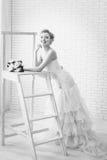 Brud i bröllopsklänning med blommor och trappuppgången Royaltyfria Bilder