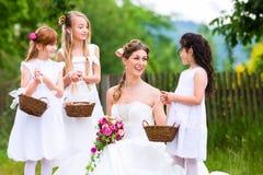 Brud i bröllopsklänning med brudtärnor Arkivbild