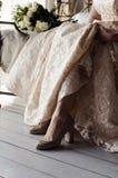 Brud i bröllopsklänning och skor royaltyfri bild