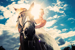 Brud i bröllopsklänning som rider en häst, backlit Arkivfoton