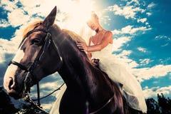 Brud i bröllopsklänning som rider en häst, backlit Royaltyfri Bild