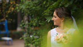 Brud i bröllopsklänningen med buketten i lager videofilmer