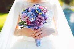 Brud i bröllopsklänningen som rymmer den brud- buketten Arkivbild