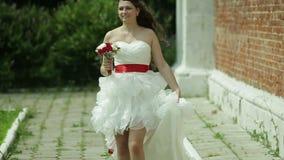 Brud i den korta bröllopsklänningen med buketten arkivfilmer