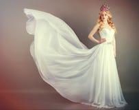 Brud i den vita bröllopsklänningen på en grå bakgrund arkivfoto