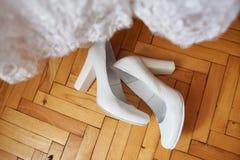 Brud i den vita klänningen Brud- skor och att skyla på trägolvet på att gifta sig morgonförberedelsen royaltyfria bilder