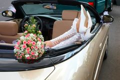 Brud i en cabriolet med blommor royaltyfri foto
