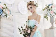 Brud i en härlig turkosklänning i förväntan av bröllop Blondinen snör åt in klänninghavsgräsplan med en bukett lycklig brud Arkivfoto