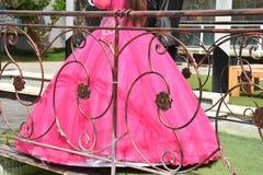 Brud i en rosa klänning bak ett mönstrat metallstaket Fotografering för Bildbyråer