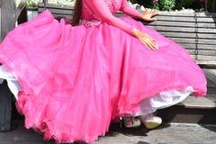 Brud i en rosa klänning för en hina på en gunga i trädgården Royaltyfria Foton