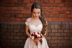 Brud i ett bröllopsklänninganseende på bakgrunden av en vägg för röd tegelsten arkivbilder
