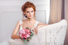 Brud i härligt klänningsammanträde som inomhus vilar på soffan arkivfoto