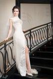 Brud i lång vit klänning på trappa Arkivbilder