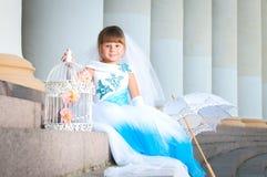 brud little En flicka i en frodig vit- och blåttbröllopsklänning och Royaltyfri Fotografi